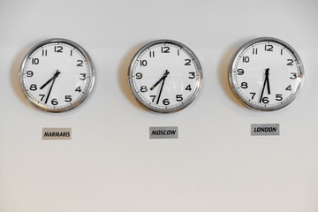 Clocks showing time in different cities on wall in hotel