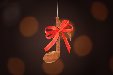 Christmas music concept. Decorative note with bow on blurred background