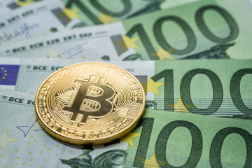 Bitcoin Münze mit Euroscheinen