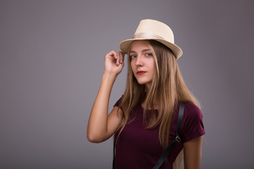 Confident in her style.Girl dreessed in hat and suspenders. Beautiful young blond hair women adjusting her hat while standing against grey background