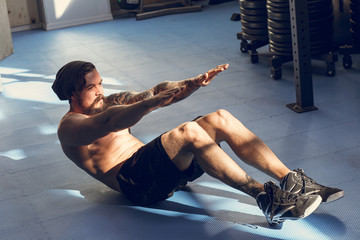 Handsome muscular man doing sit-ups on gym floor