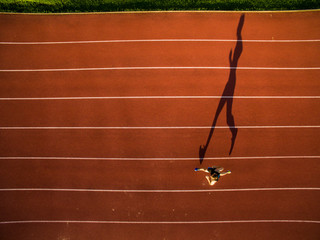 Shot of a young male athlete training on a race track. Sprinter running on athletics tracks seen from above.