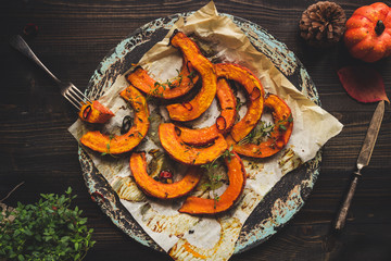 Delicious baked pumpkin with thyme and chilli on the wooden table, top view