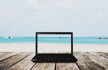 Computer laptop on wooden table with the beach view background. Clipping path on screen