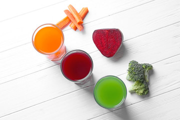 Fresh vegetable juices in glasses and ingredients on wooden table