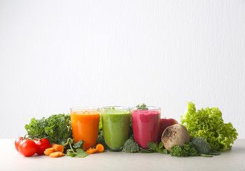 Fresh vegetable juices in glasses and ingredients on white background