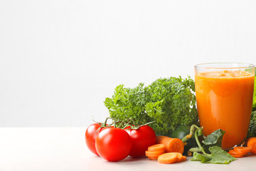 Fresh juice in glass and ingredients on white background