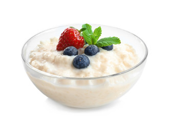 Creamy rice pudding with berries in glass bowl on white background