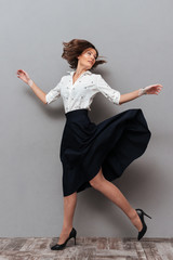 Full-length image of woman in business clothes running in studio