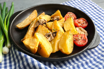 Frying pan with delicious baked potato wedges on napkin