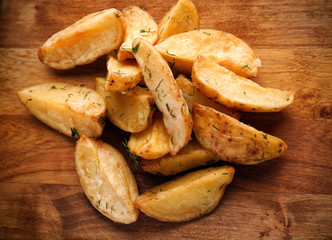Delicious baked potato wedges on wooden background