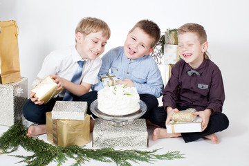 boys holding a cake among gifts