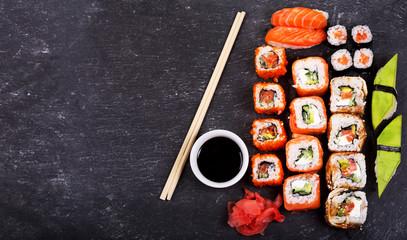 sushi rolls set and sashimi on dark background