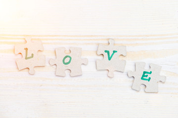 Word Love made of four pieces of jigsaw puzzle on light wooden table in rays of the sun