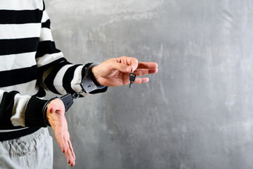 unidentified hands of prisoner in prison stripped uniform standing in handcuffs and holding a key in the dark interrogation room, copyspace for text. Concept of expiration