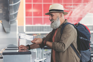 Cheerful grandfather holding out card at airport