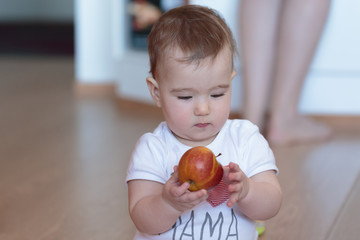 Little child with a red apple in his hands.