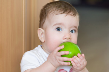 Small child with a big green apple. A child bites an apple with a surprised look.