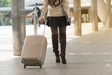 Travel young woman legs pulling suitcase bag walking along in modern city.