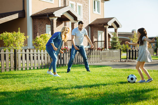 Little girl playing football with her parents
