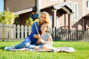 Charming mother and daughter taking selfies in the yard