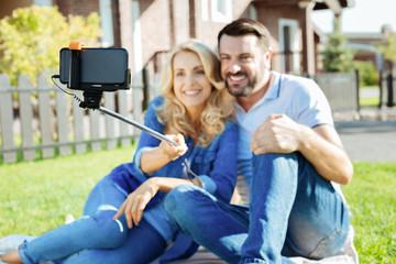 Lovely couple using selfie stick on picnic