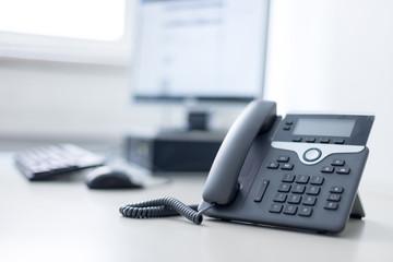 Arbeitsplatz mit Telefon, Computer im Hintergrund