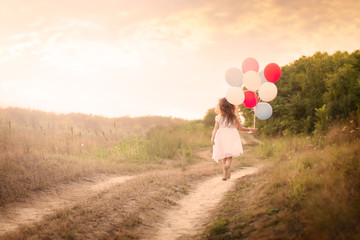 Little girl with colorful balloons at the meadow - Back view