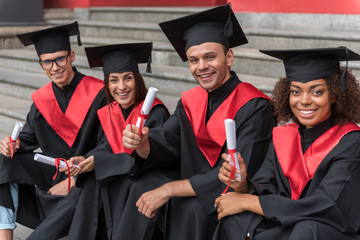 Glad young students sitting on steps in graduation clothes