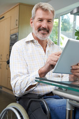 Portrait Of Disabled Man In Wheelchair Using Digital Tablet At Home