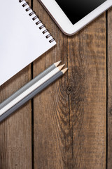 Modern wooden office desk table with tablet, note book, pens, businesscard. Place for typography and logo. Flat composition