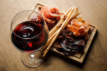 Glass of red dry wine and several kinds of cured meats on a wooden board