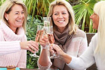 Three mature girlfriends with glasses of sparkling wine