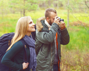 Young beautiful couple walking in forest and taking pictures. Camp, tourism, hiking concept.