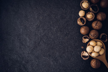 Close up Macadamia nuts and copy space on dark black stone background , superfood and healthy food concept , overhead or top view shot