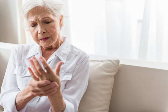 Elderly lady is enduring strong ache