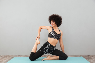 Pretty curly fitness woman make sport yoga exercises