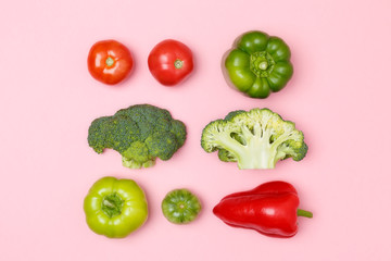 Top view of broccoli, green pepper, tomatoes, red paprika on a pastel pink background. Set of seasonal vegetables. The concept of a healthy diet