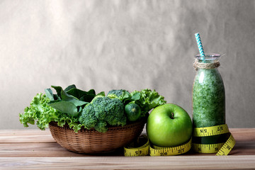 Healthy fresh  green smoothie juice in the glass bottle on wooden table with green apple and  vegetables basket for healthy detox and diet  habits concept
