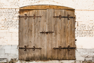 Aged Old Wooden Door With Lock On Old Brick White Wall. Ancient Style.