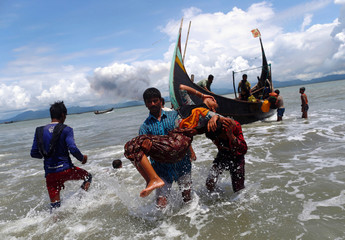 Smoke is seen on Myanmar's side of border as an exhausted Rohingya refugee woman is carried to the shore after crossing the Bangladesh-Myanmar border by boat through the Bay of Bengal, in Shah Porir Dwip
