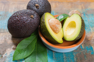Ripe fresh avocado with leaves on blue wooden table