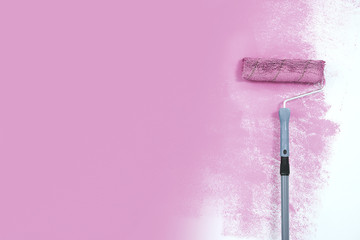 paint roller next to the pink wall.