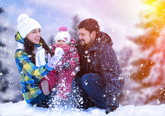 Attractive man, woman and child on a background of a Christmas landscape. Winter nature