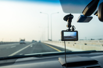 Car video camera (dash cam) inside of car on highway with blurred background of highway road, from perspective of the driver. Concept of safety camera for car protection, technology for safety