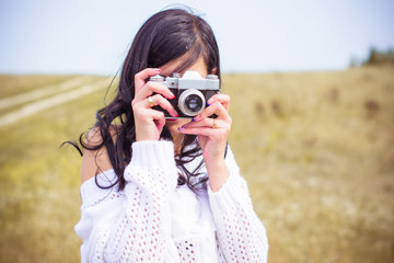 A young amateur photographer with an old camera in the field takes pictures of the neighborhood. Girl with a photo camera on the nature have a good mood on a vacation