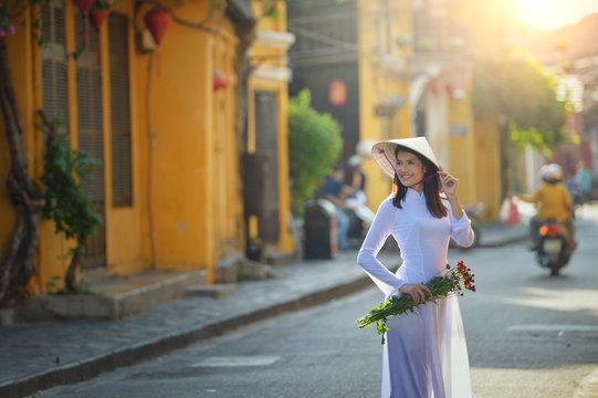 Portrait of a woman in street holding flowers, Vietnam