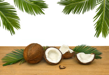 Coconut (Cocos nucifera) with half and palm leaves on wooden table on a white background.