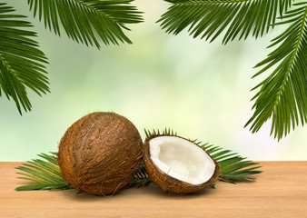Coconut (Cocos nucifera) with half and palm leaves on wooden table on a background tropical leaves palm tree
