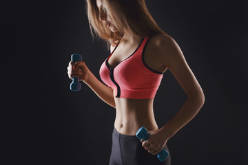 Fitness model woman with dumbbells at studio